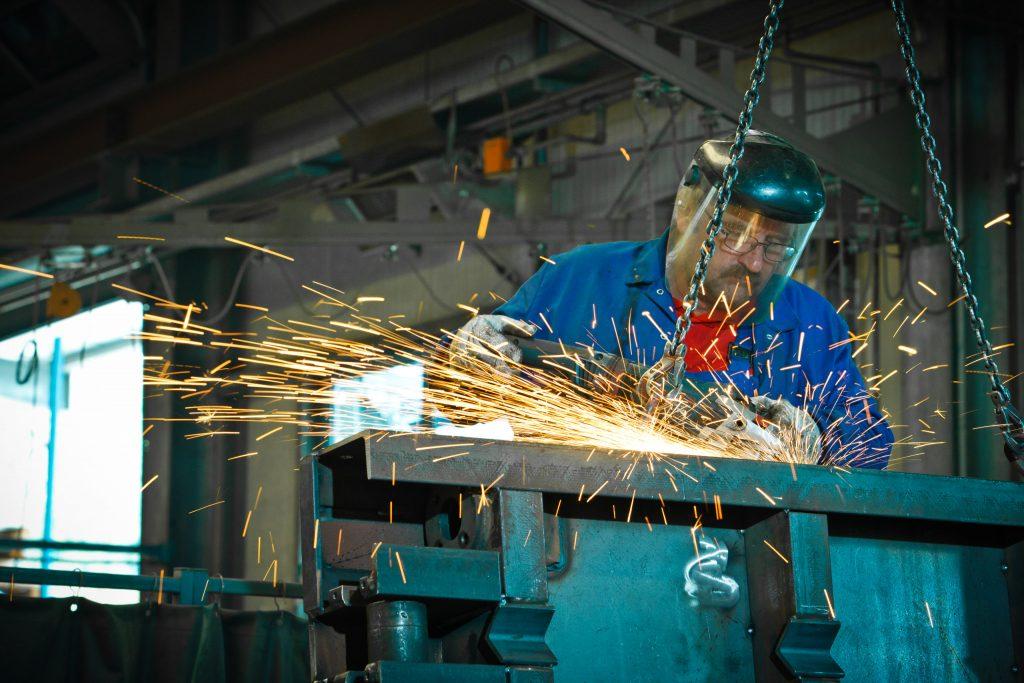 Arbeiter bei präzisen Schweissarbeiten der Mutter Metalltechnik.